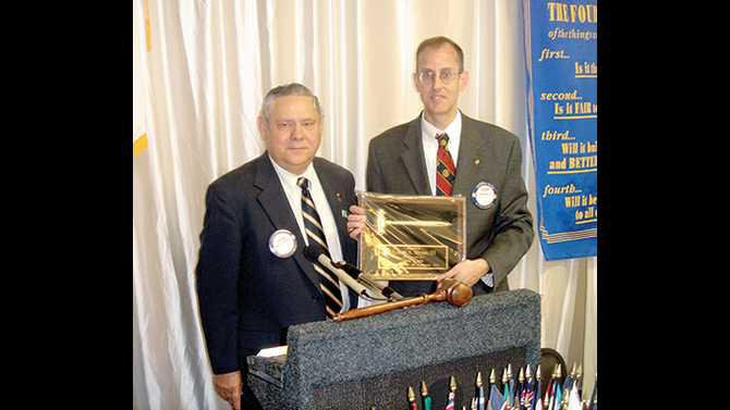 Conyers-Rotary-torch---Wilson-Mathews-passes-torch-to-new-president-Albert-Myers-III-during-the-Installation-Banquet-June-21