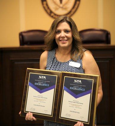 Sherri Davis holding two awards