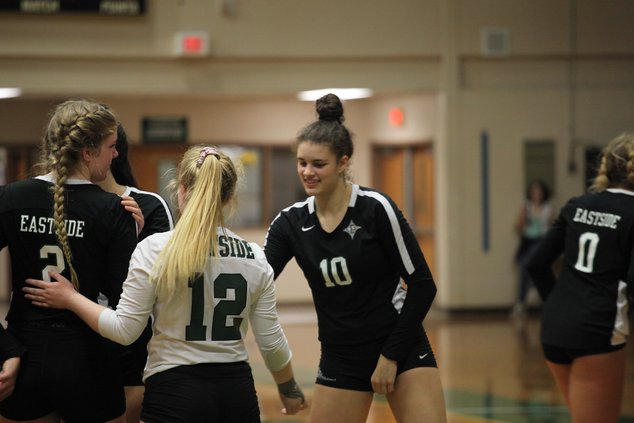 Junior Taylor Adams celebrates a point with freshman Payton Robinson and junior Hailee Bell